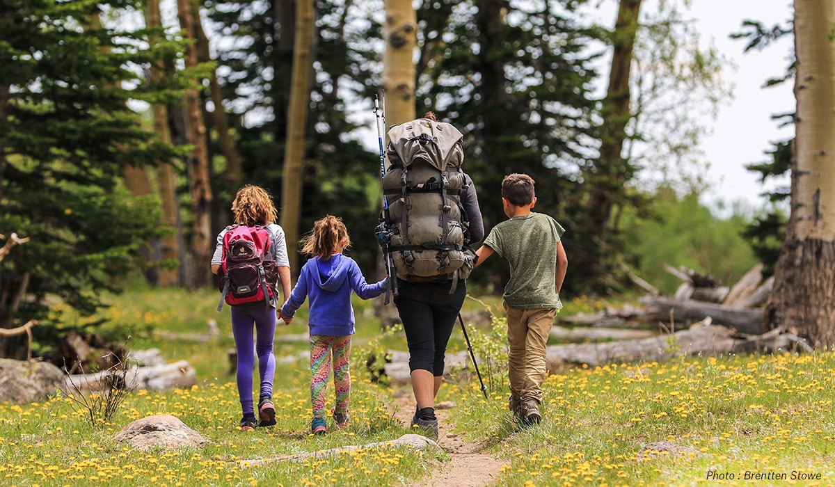 Woman backpacking or hiking in the mountains with three children.