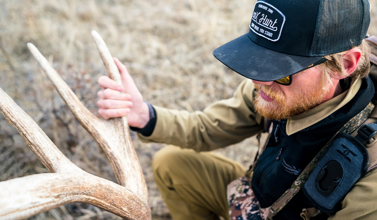 Montana hunting photographer and onX Ambassador Steven Drake with an elk shed found while shed hunting.