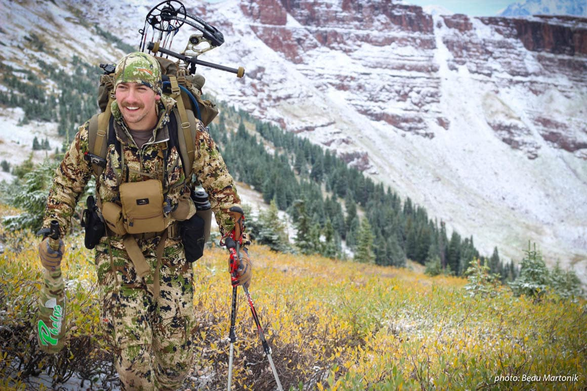 Man climbing mountains while hunting in the mountains.