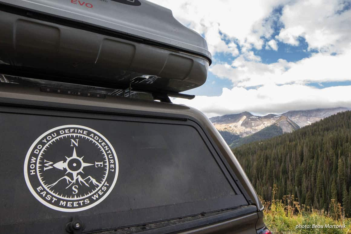East Meets West truck with logo in mountains.