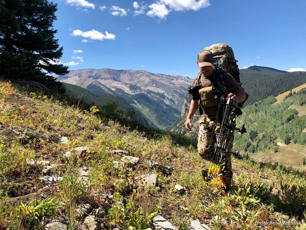 Man bowhunting in mountains with pack, bow and camouflage.