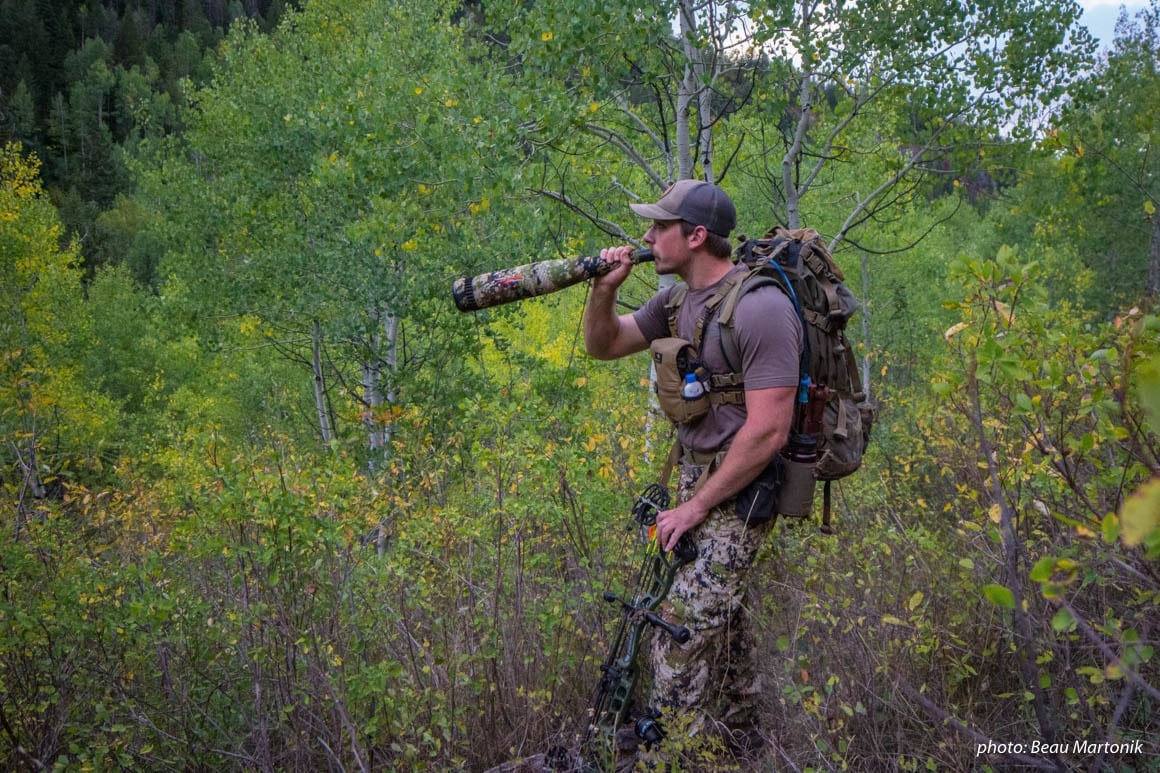 Man bugling for elk while hunting in the mountains.