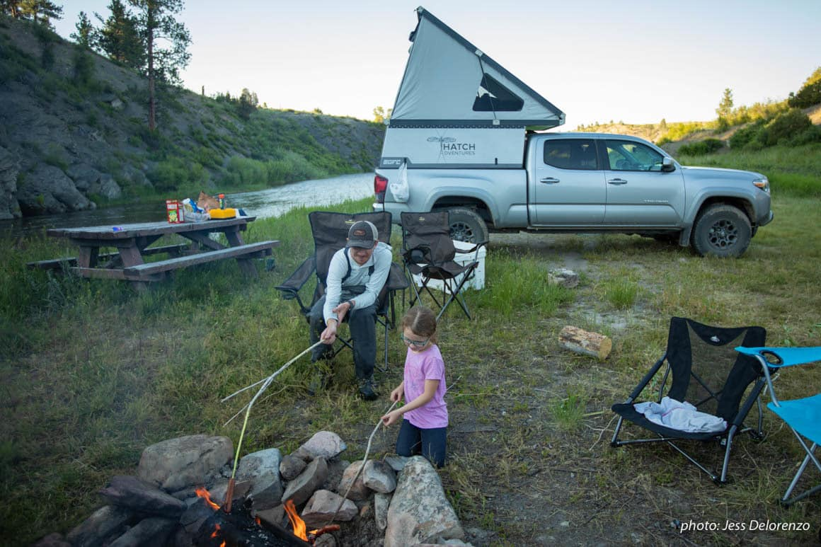 Father and daughter at campfire while truck camping in Montana.
