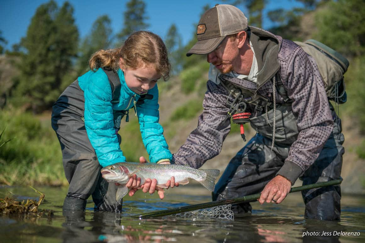 Father and daughter netting trout while fishing in a river.