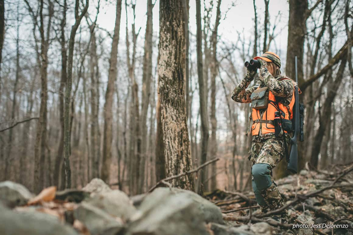 Woman looking through binoculars while hunting in the Northeast with a rifle.