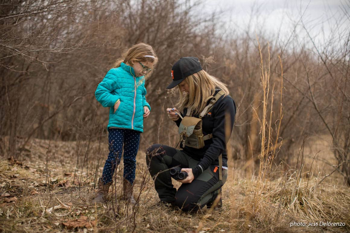 Woman and girl in woods looking at shed antlers.