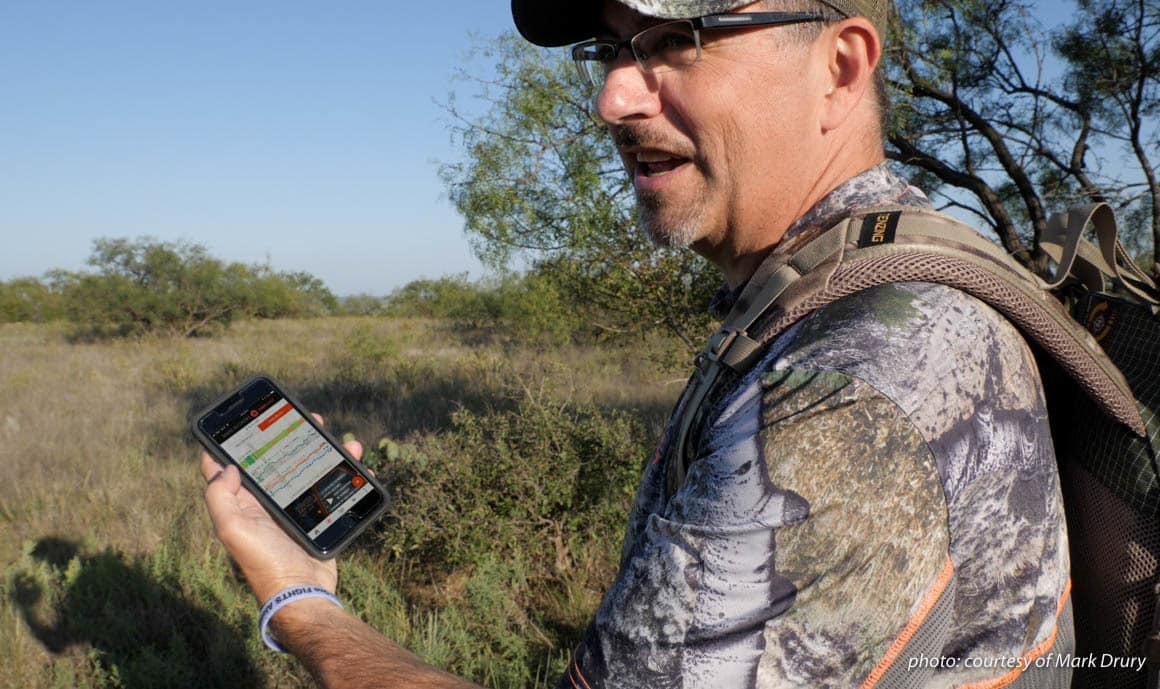 Image of Mark Drury of Drury Outdoors using the DeerCast app on his phone while hunting.