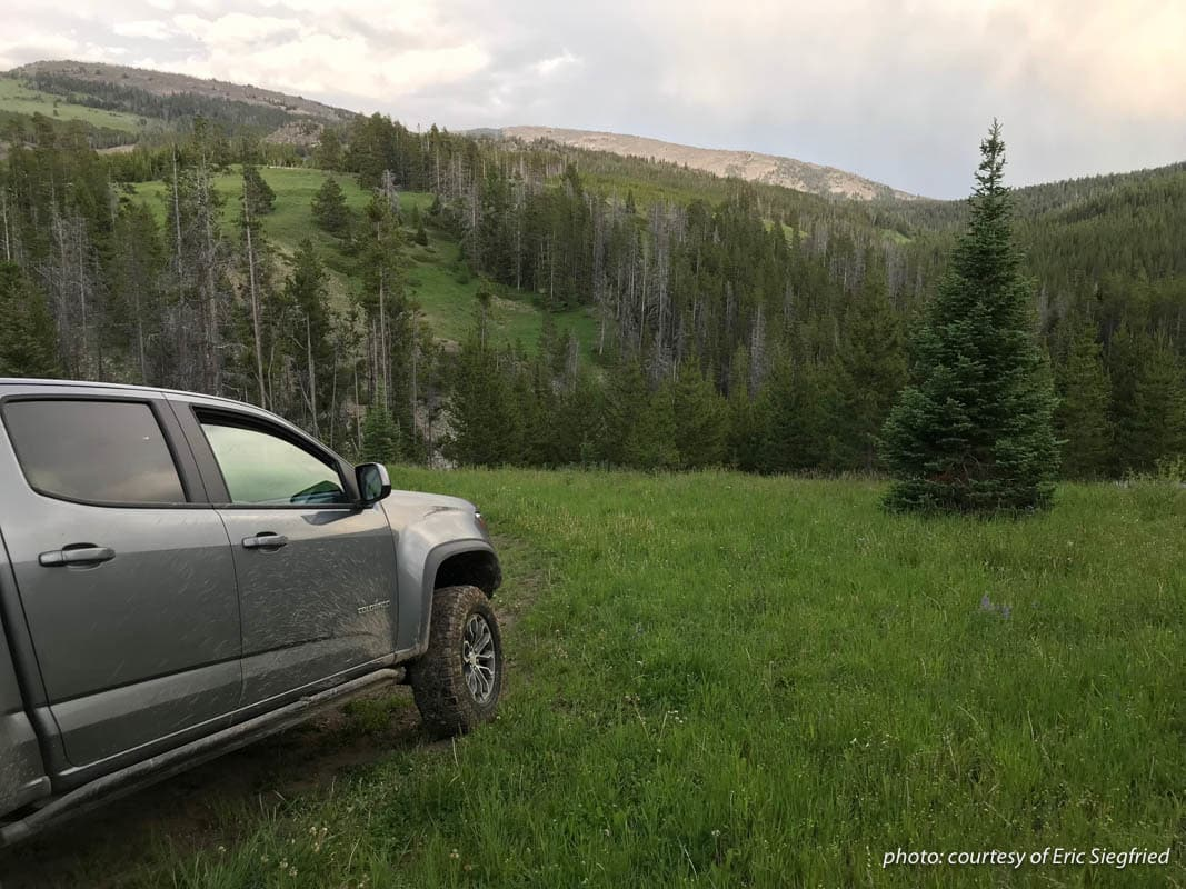 Muddy truck parked near the mountains of Montana.