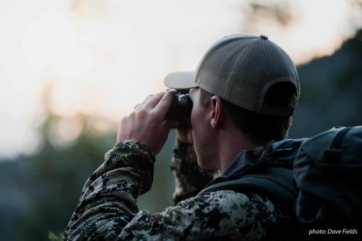 Man in camouflage uses binoculars to spot elk while hunting in the Montana backcountry.