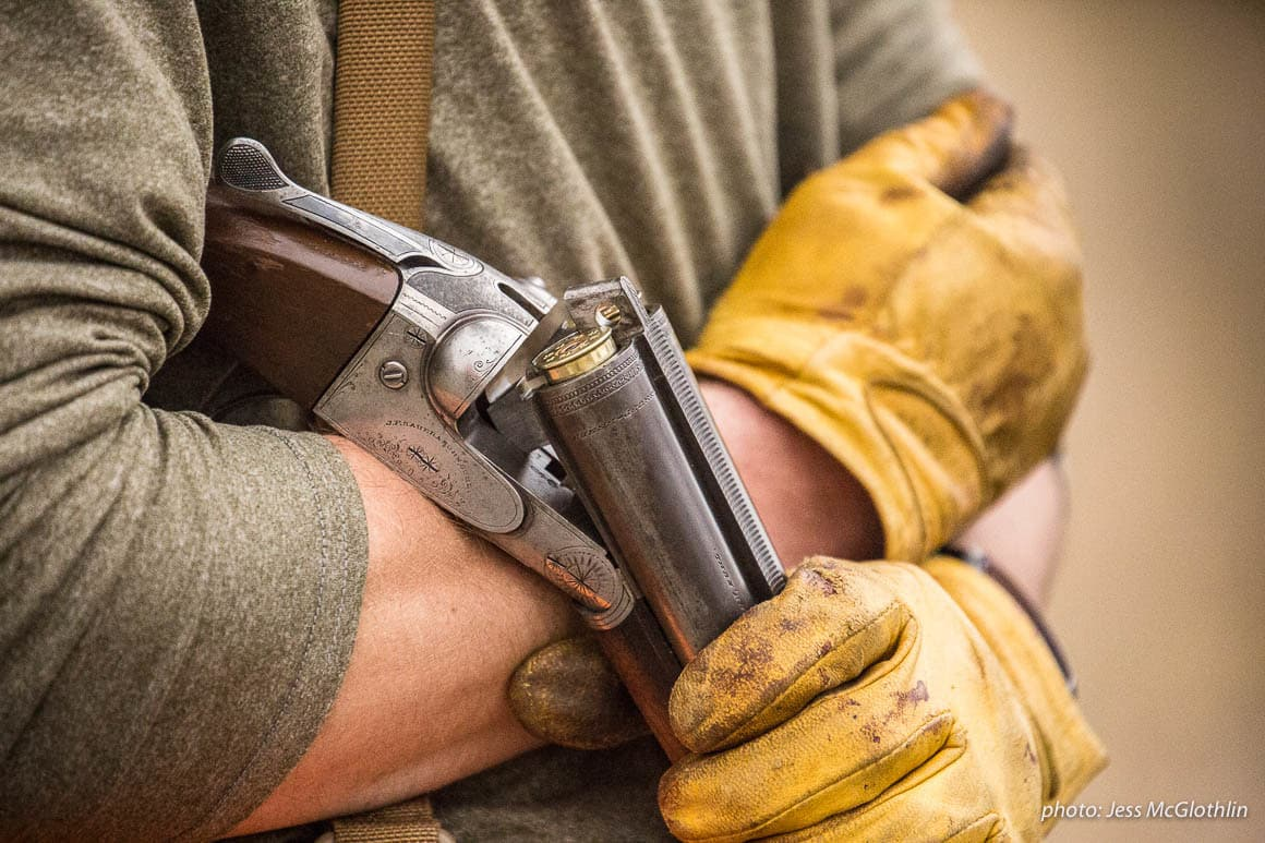Details of a shotgun, strap vest and worn leather gloves on a hunter while upland bird hunting in eastern Montana.