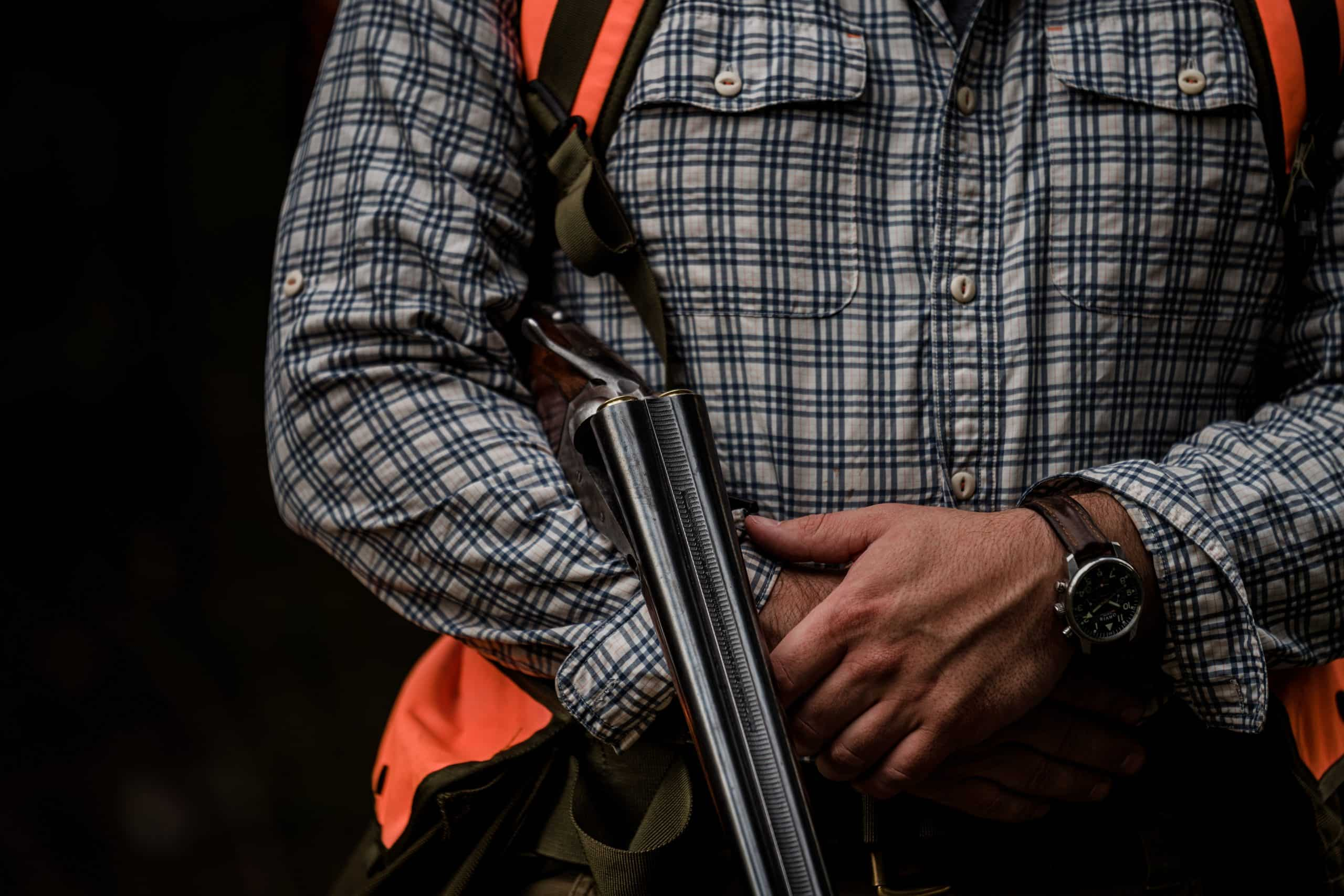 A hunter holds a side-by-side shotgun while grouse hunting in northwest Montana.