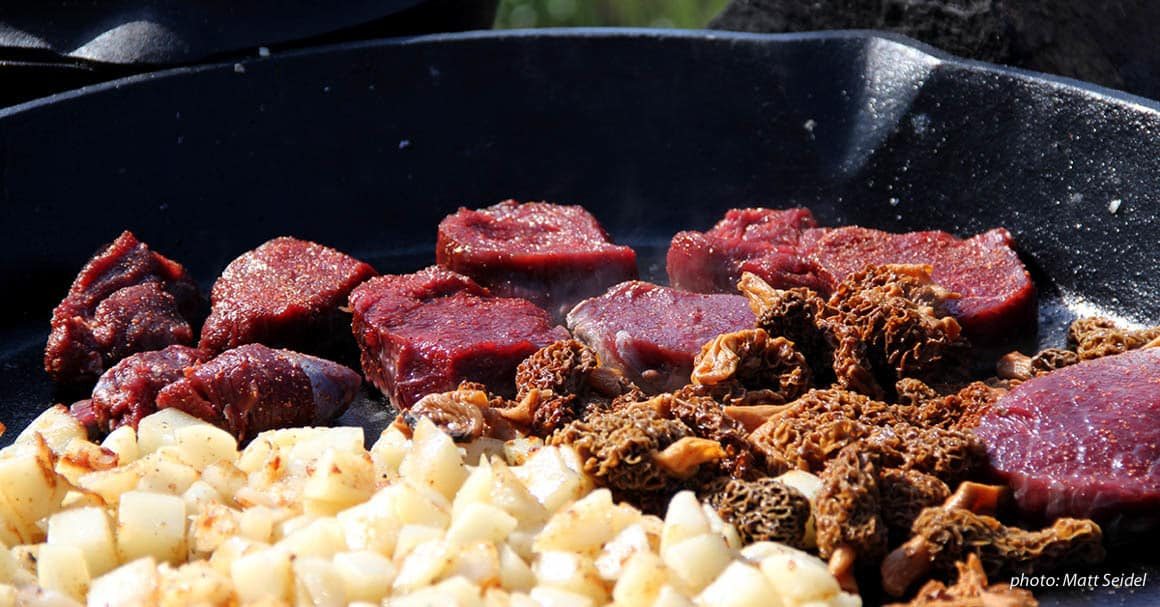 Game meat, morel mushrooms and potatoes in a large cast-iron skillet.