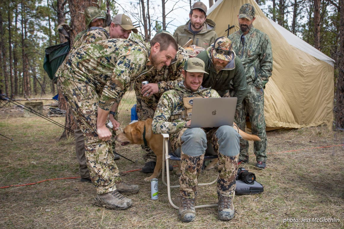Hunters gather around a computer while in a wall tent camp in Montana.