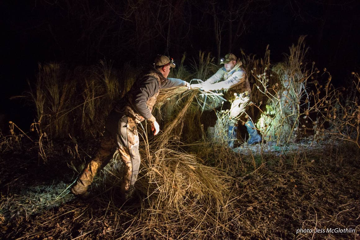 Two men work to set up a goose blind by headlamp.