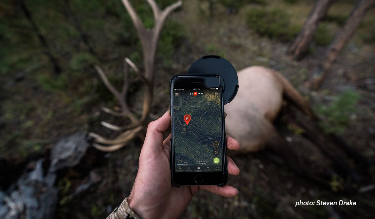 A hunter stands over an elk looking at onX Hunt with an elk Waypoint.