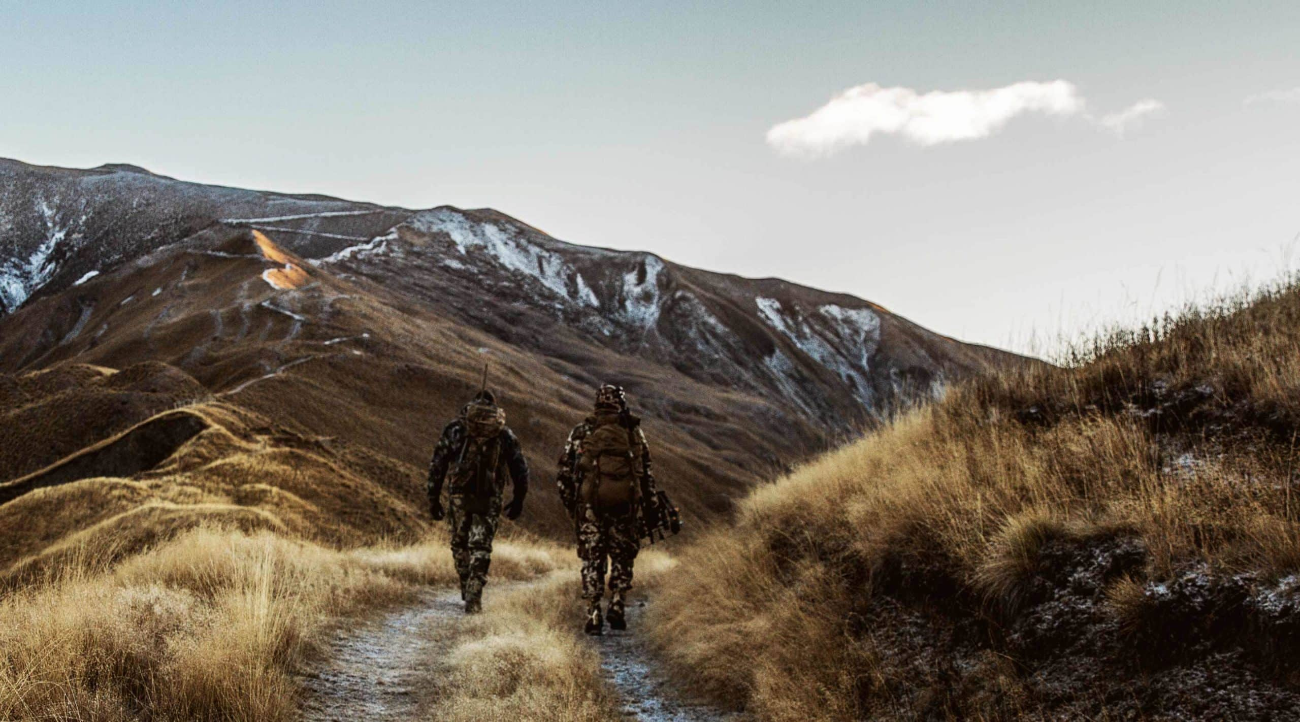 Two men in camouflage walk into the mountains in morning to hunt.