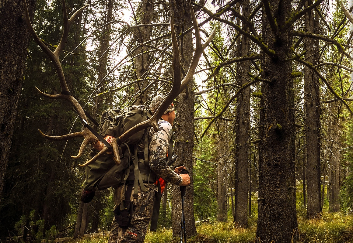 onX Hunt Founder Eric Siegfried packing out an elk while hunting in the mountains.