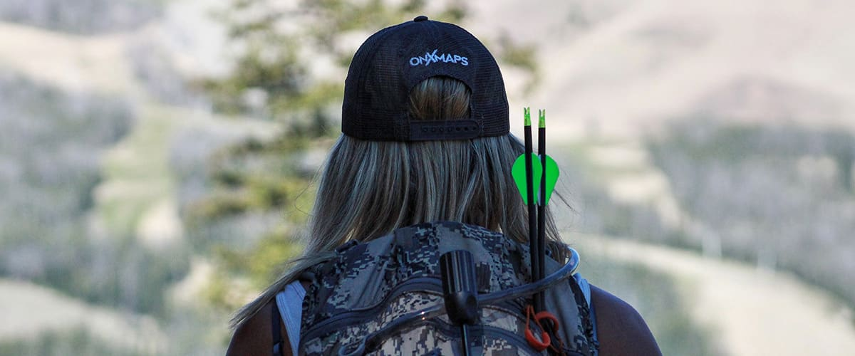 Female bowhunter with onX Hunt cap with camouflage backpack.