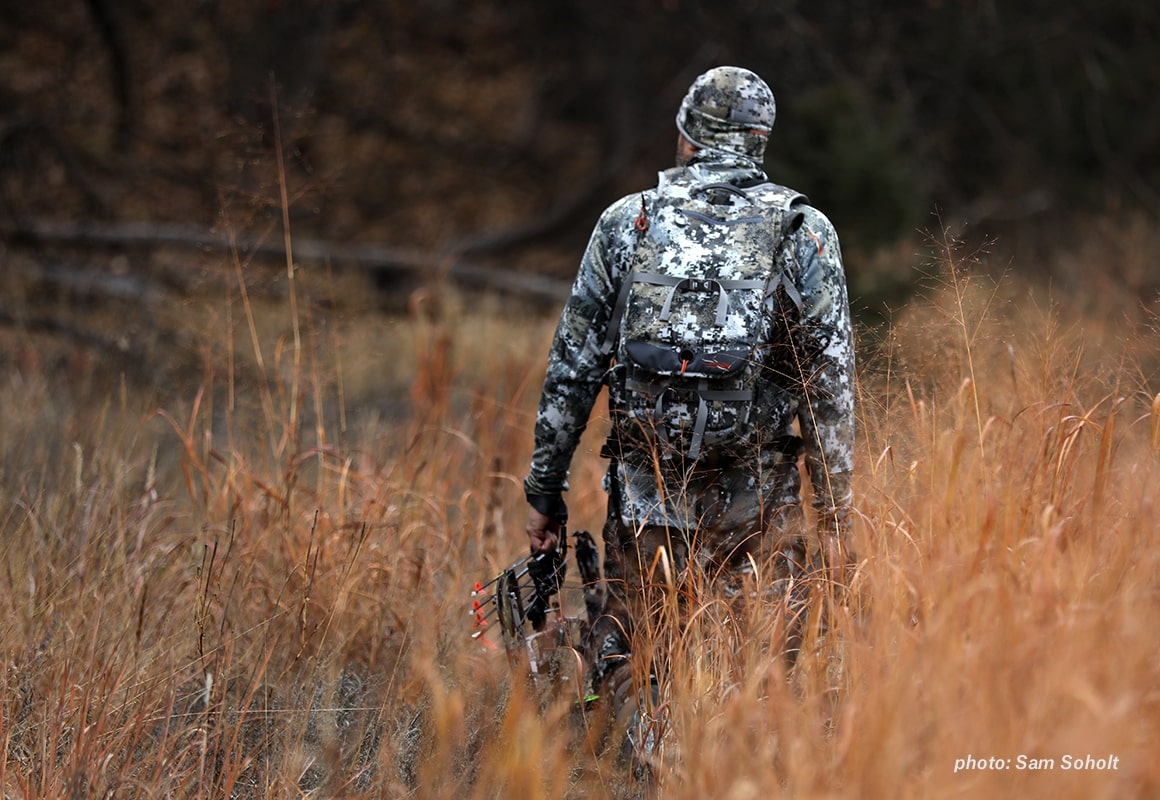 Image of a man in camouflage walking through autumn grass with a bow in hand while hunting.