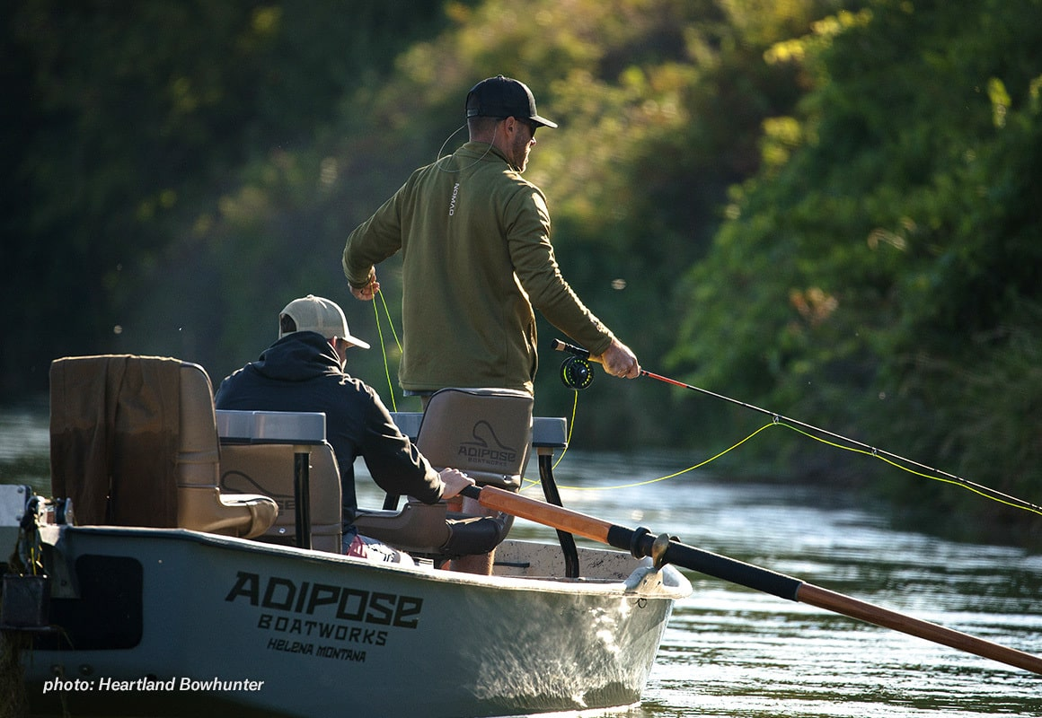 Two men fly fishing from a driftboat in the summertime.