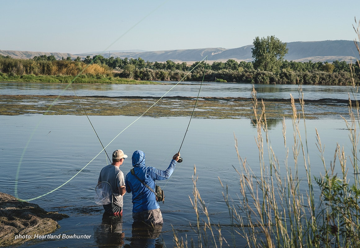 Two men fishing a river in the summertime with fly rods.