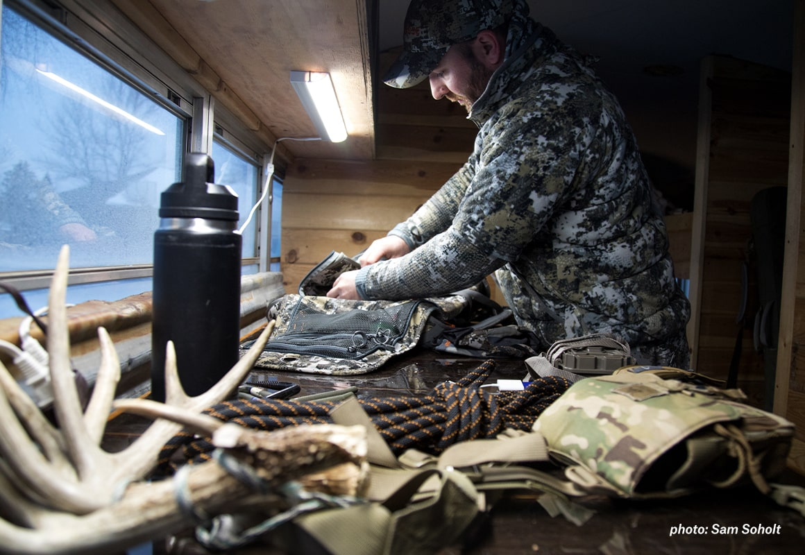 Man preparing and loading gear before heading outside to hunt.