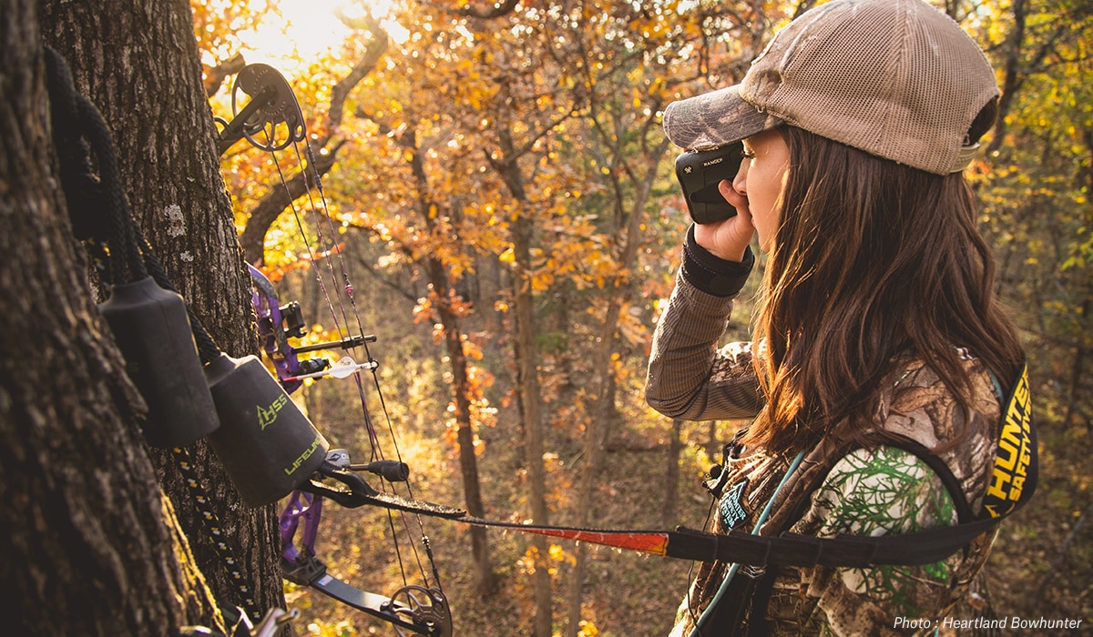 Woman in tree stand bow hunting.