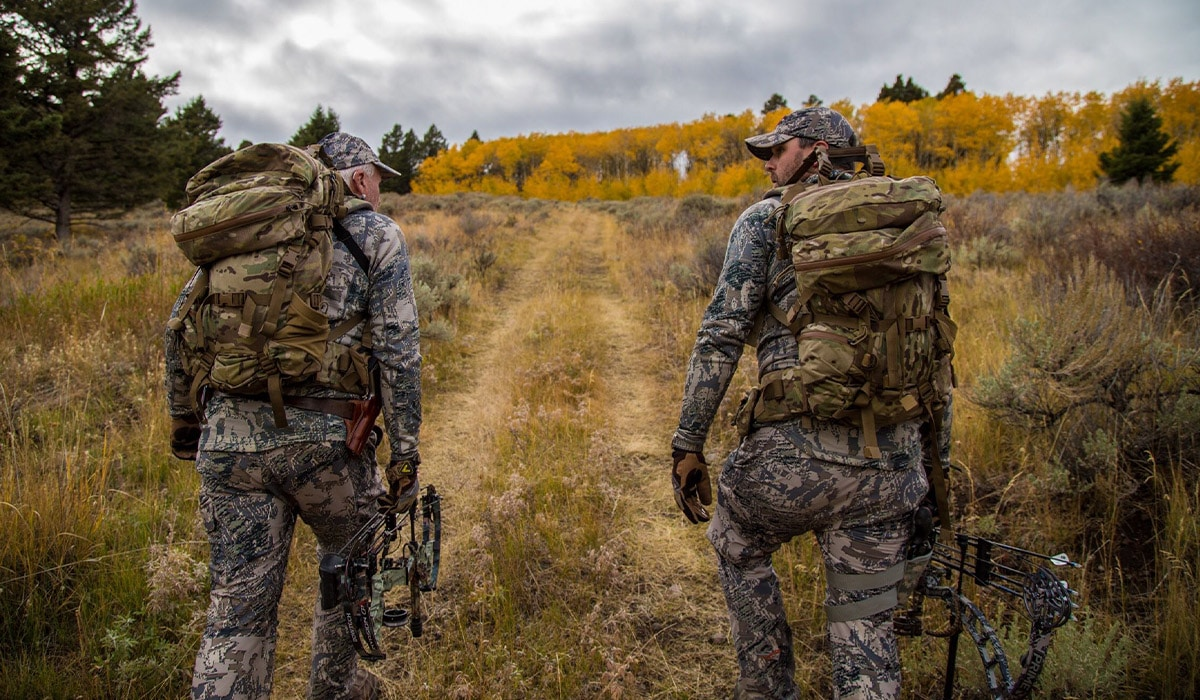 Two hunters walking on an overgrown dirt road accessing public land using an access easement.