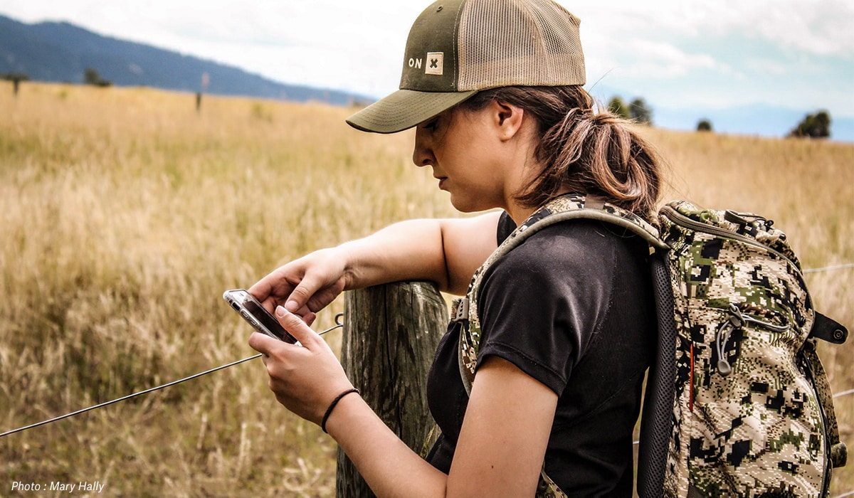 Woman looking at phone while hunting and hiking beside fenceline.
