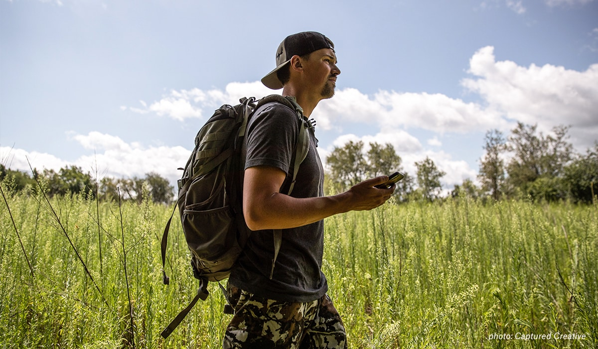 Mark Kenyon walks though a field with his onX Hunt App on his phone.