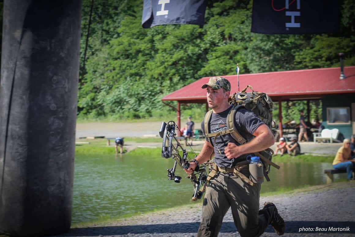 Man running with pack and bow in Hike to Hunt fitness competition.