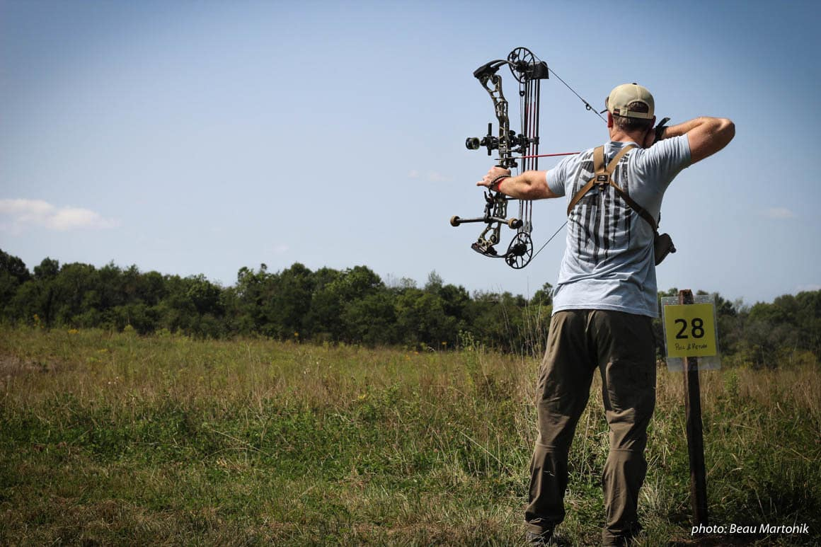 Man practicing compound bow in field.