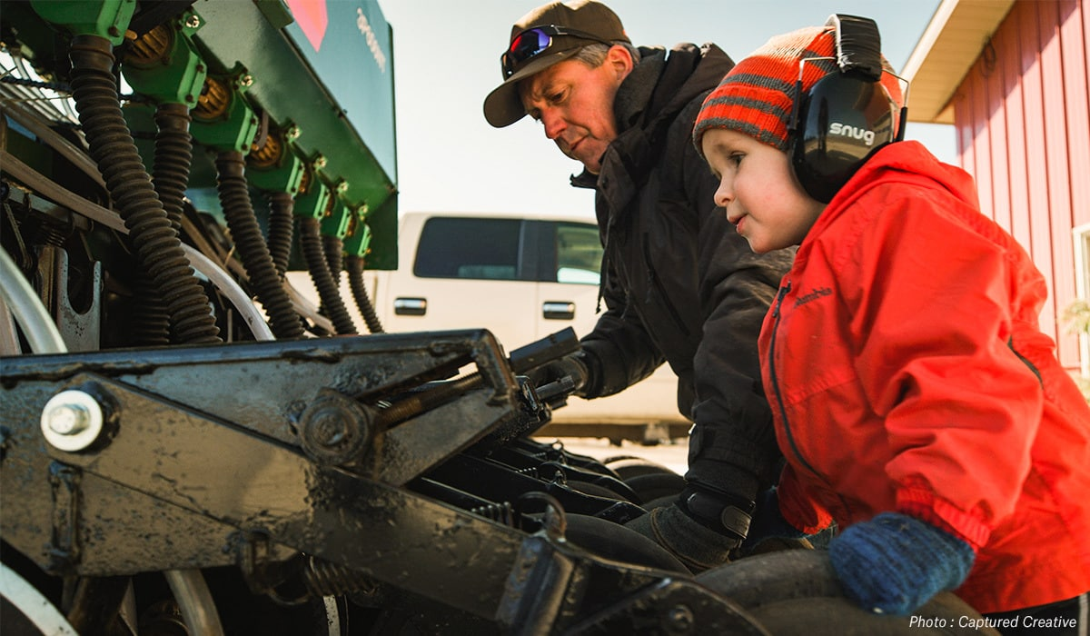 Taylor Kollman's father and son inspecting equipment on their Minnesota hunting property.