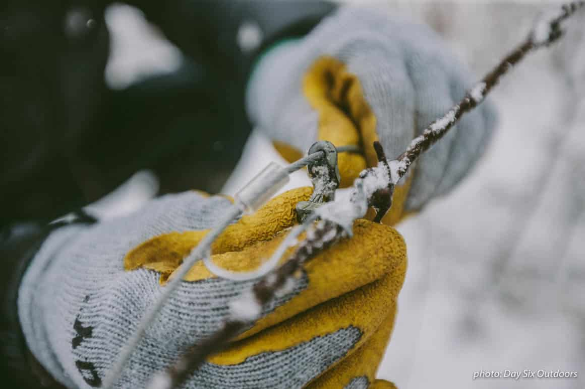 Man holding snare trap with gloves in the snow while trapping animals in the woods.