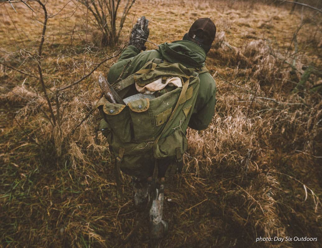 Man with backpack hiking and hunting as he sets up traps in the woods in the fall.