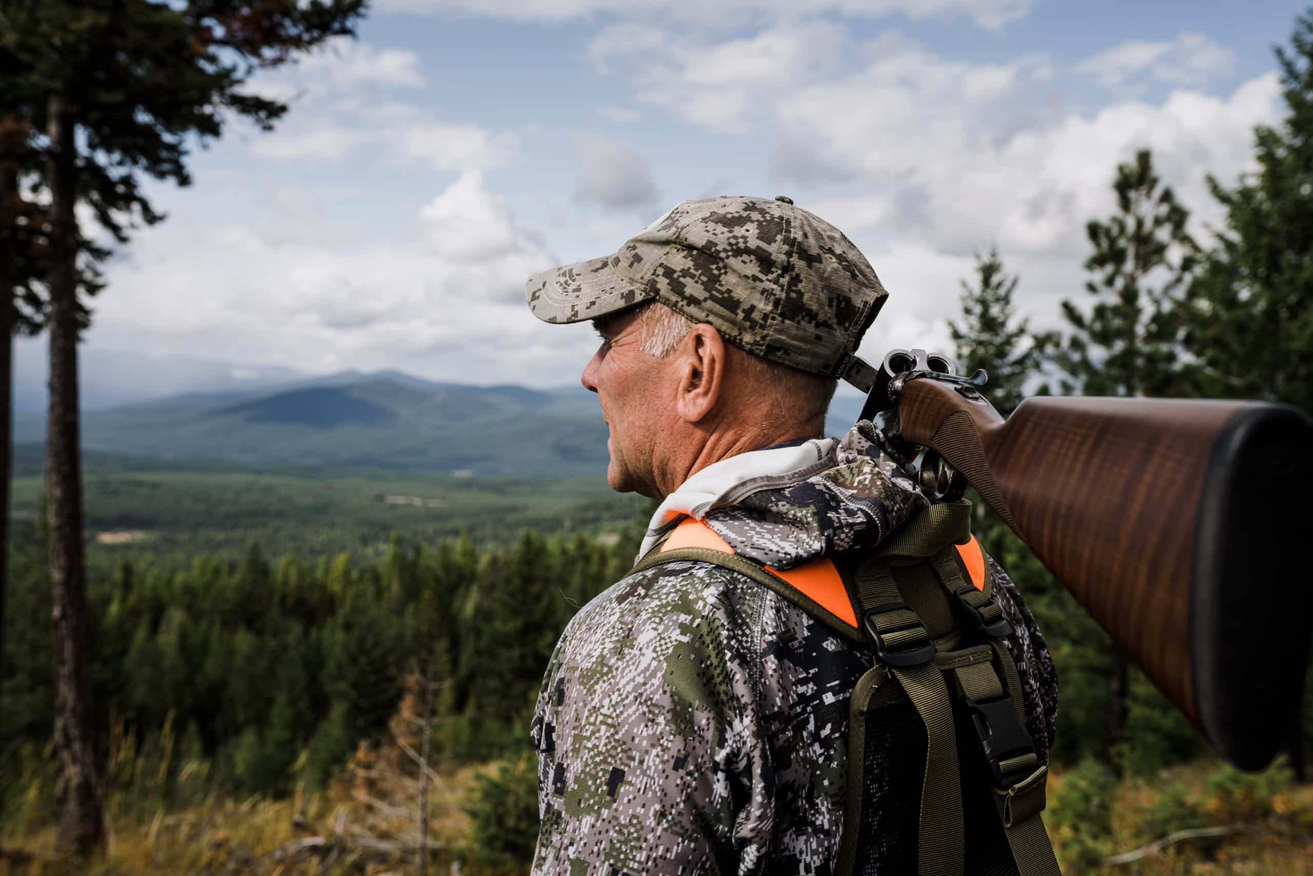 Montana outfitter Tim Linehan holds a shotgun and looks out over the valley.