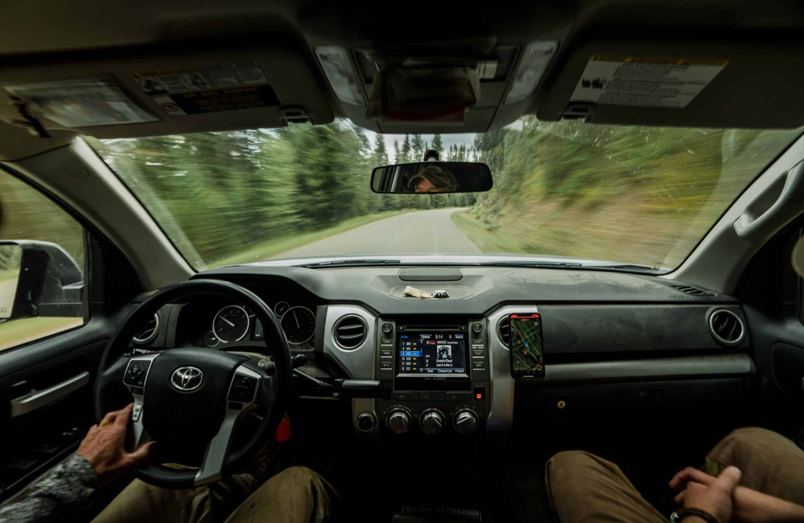 Two hunters ride in a truck while looking at the onX Hunt App.