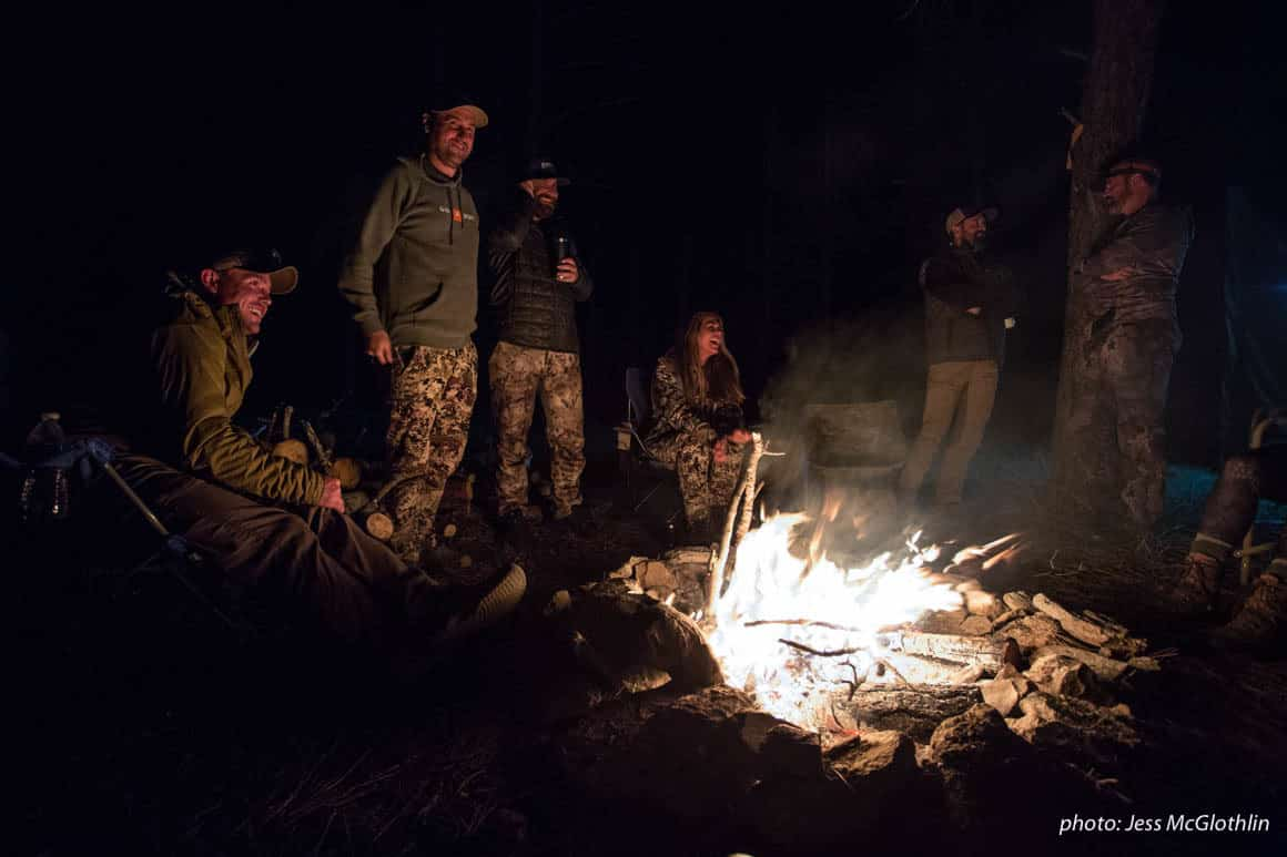 Men and women gathered around a campfire while hunting in Montana.