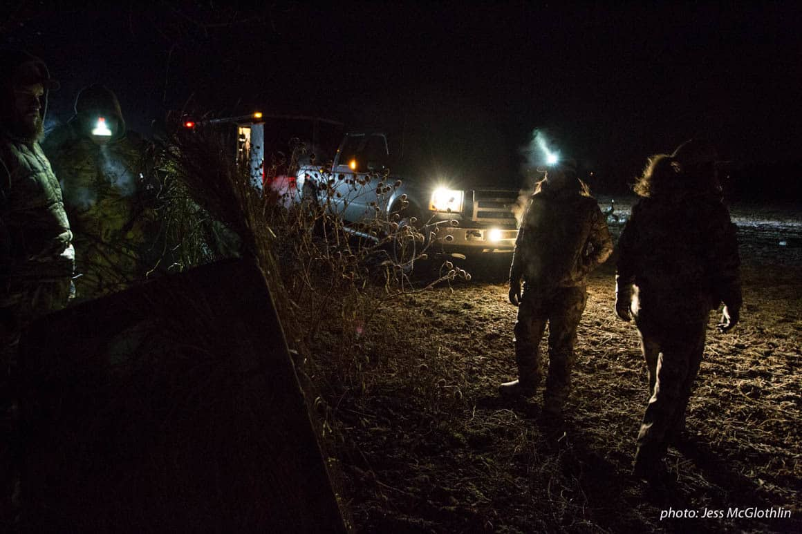 Waterfowl hunters set up decoys and a blind in darkness by the light of truck headlights.