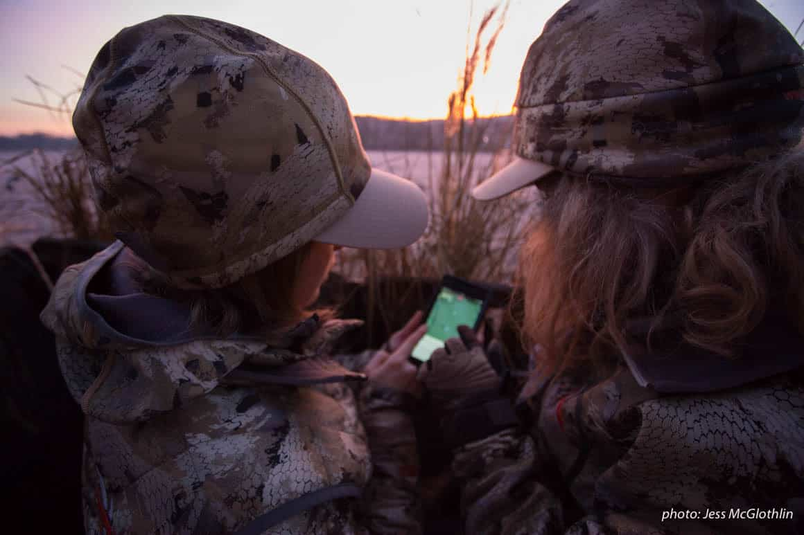 Two female hunters look at the onX Hunt App while in a goose blind at sunrise in New Jersey.