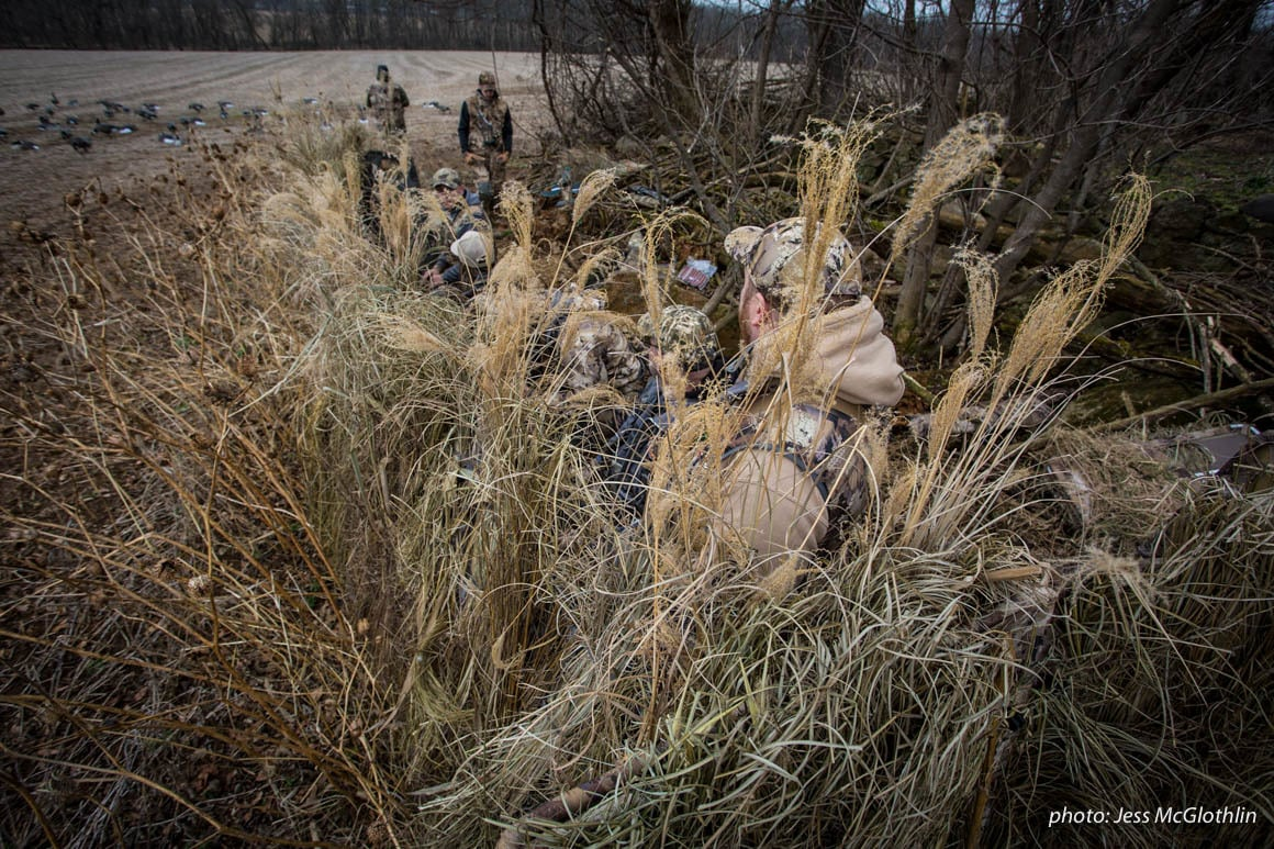 Waterfowl hunters in a goose blind in a field during winter.