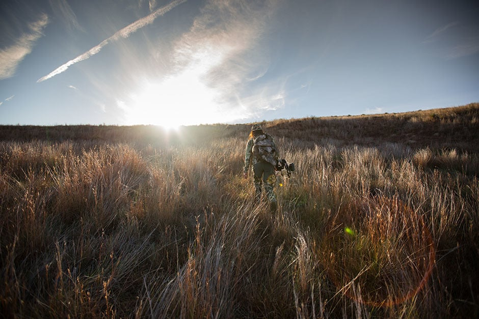 Image of female hunter in camo with a bow walking into the sunset in a field on Western public lands.