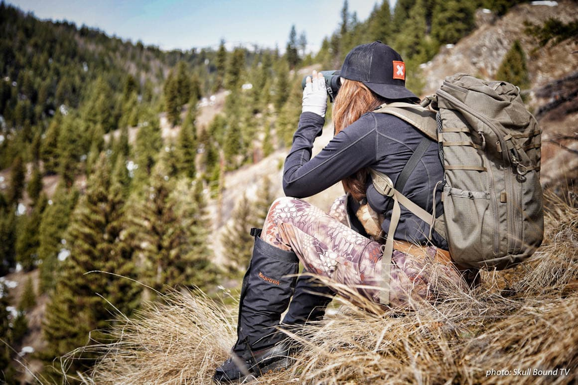 Woman in camouflage glassing for animals while hunting in the mountains.