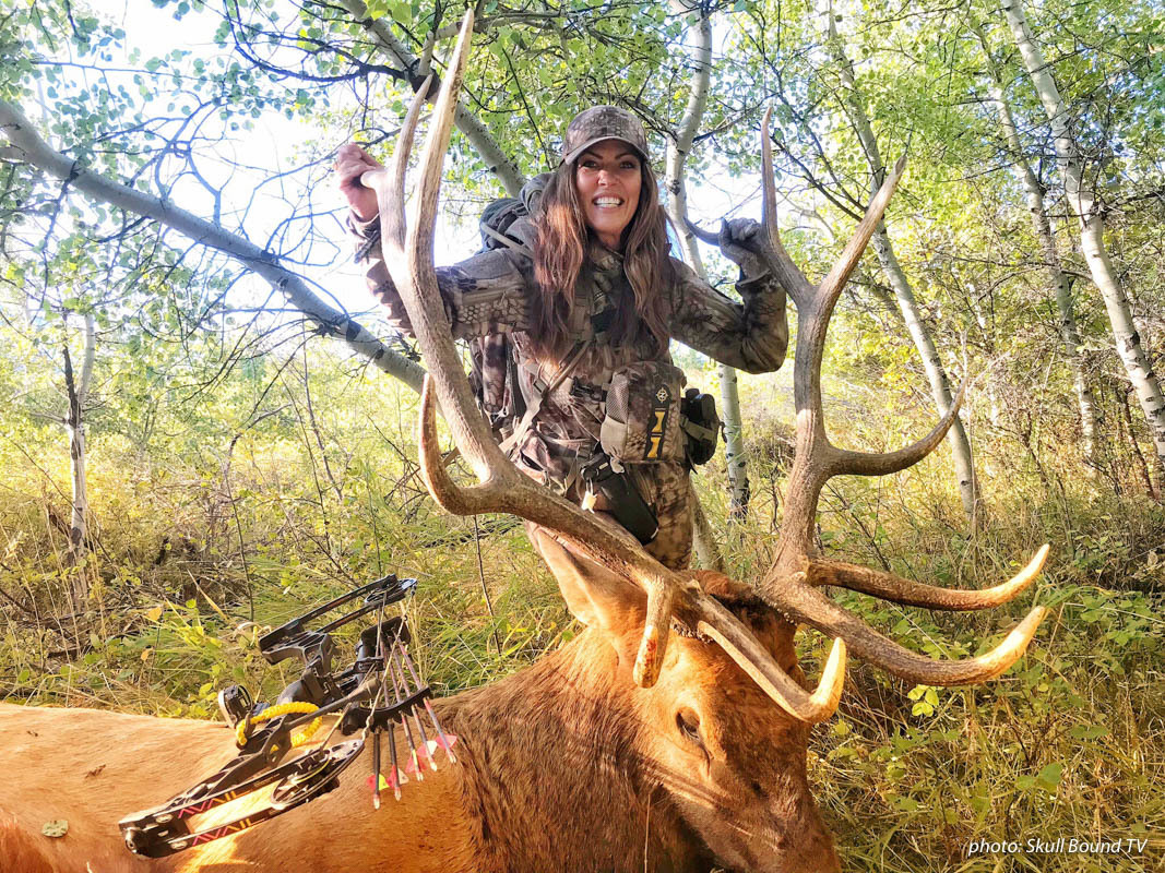 Women bowhunting with elk she shot.