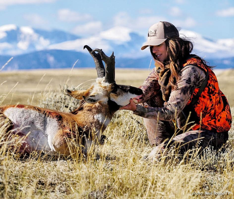 Female hunter hunting in the plains with antelope she shot.