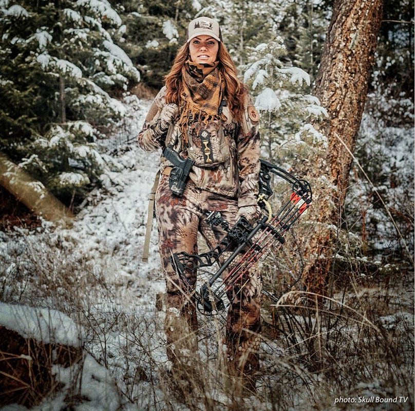 Woman in camouflage hunting in the snowy woods holding a compound bow.