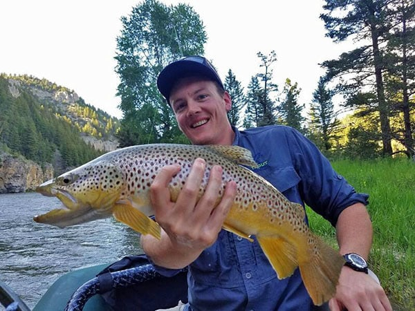 Man holding large brown trout caught while fly fishing on Montana's Smith River.