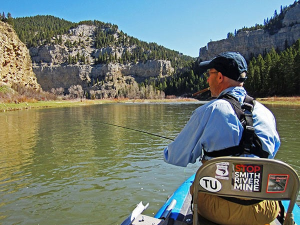 Man smoking cigar and fly fishing on the Smith River in Montana from a raft.