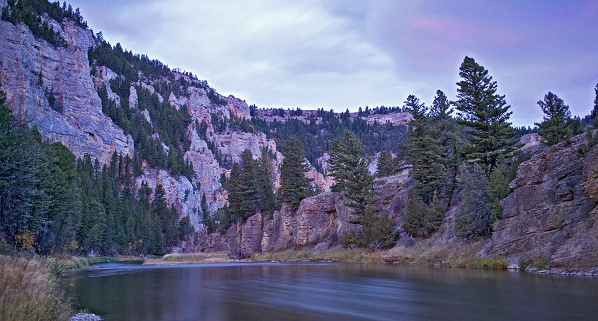 Image of the Smith River in Montana, with craggy cliffs, river and sky at sunrise.