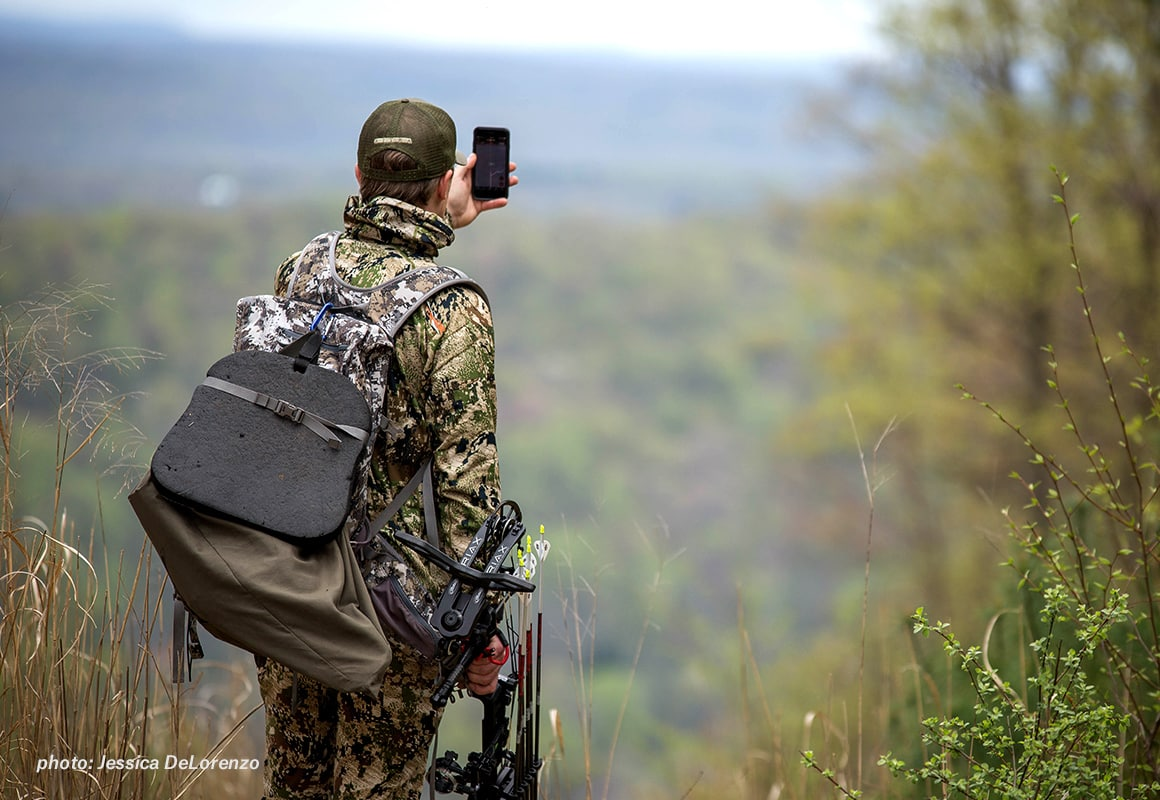 Bowhunter looking at the onX Hunt App in the backcountry